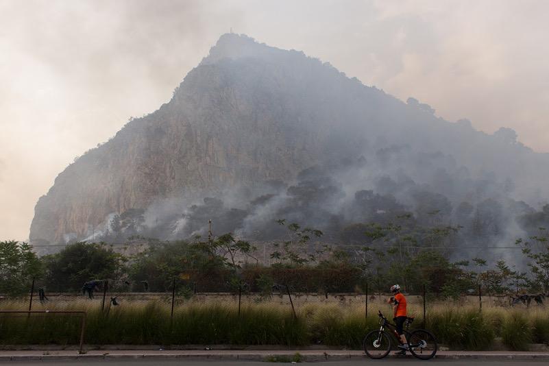Un ciclista prende fiato durante un incendio di Monte Pellegrino a Palermo